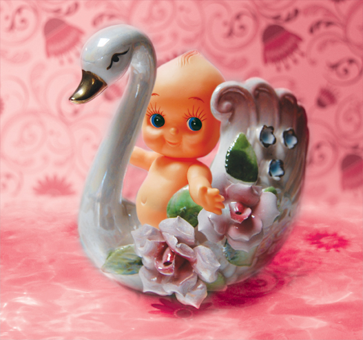 Look Mama design, kewpi baby riding a kitsch porcelain swan