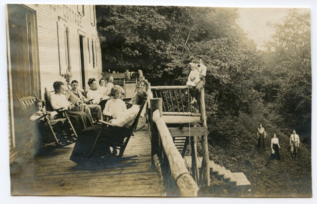 Large family sitting around on the balcony in the Adirondacks. Very old photograph.