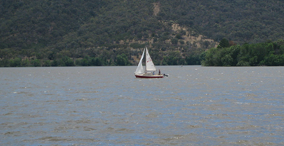 Red sailboat scooting along in the wind