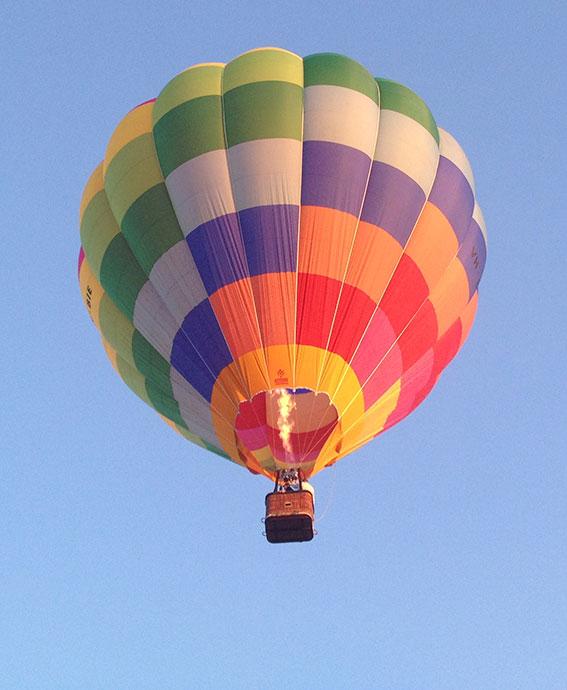 rainbow checked balloon agains a blue sky