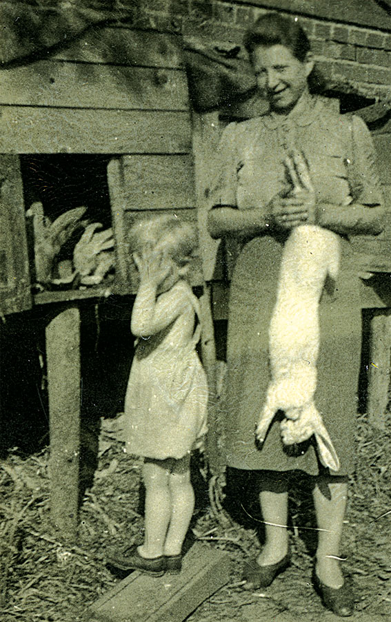 Little girl near rabbit hutch puts hands over face as mum holds large dead bunny.